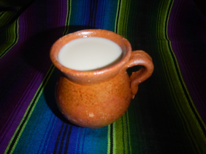 Una taza naranja contiene atol y se sienta sobre una manta de rayas azules y verdes.