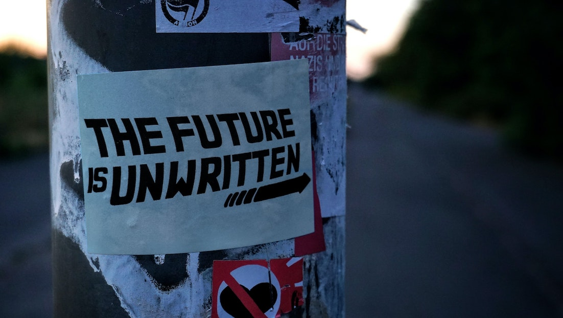 Outside adrtising pillar with a sign wrapped around it which reads 'The Future Is Unwritten'