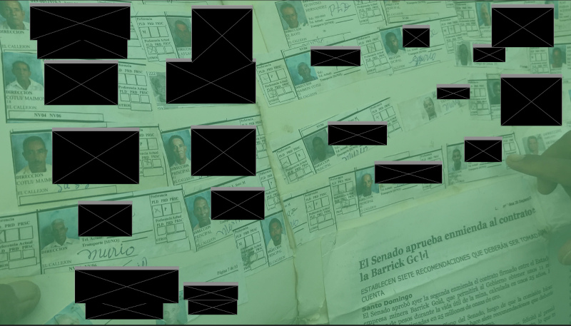 A man holds a manila folder with images of persons thought dead due to pollution related illnesses. Identifying information, such as names, are redacted with black blocks.