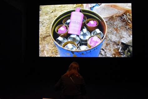 A woman with shoulder length hair stands facing a wall projection of pink tear gas canisters in a blue bucket.