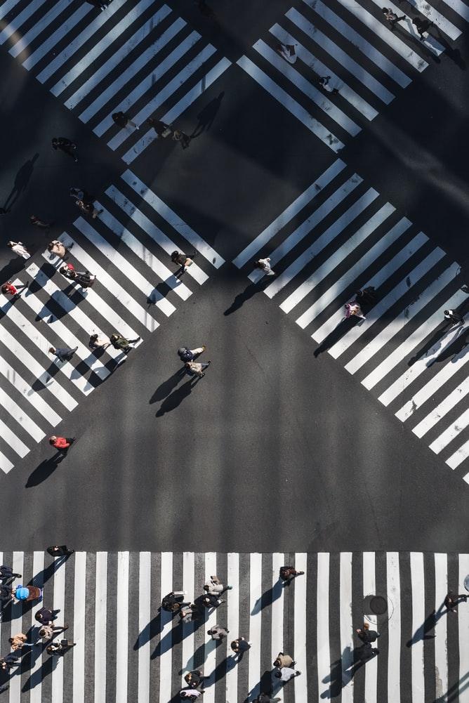 Imagen aérea de encrucijada por la que la gente cruza la calle mediante tres pasos de cebra, dos se cruzan entre sí, el tercer paso de cebra es horizontal, ubicado debajo de los dos pasos de cebra cruzados.