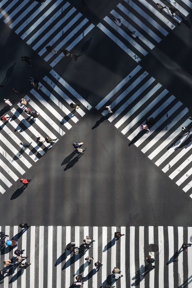 Aerial image of crossroads whereby people cross the street using three zebra crossings.Two are crossed between each other, the third zebra crossing is horizontal, located under the crossed two zebra crossings.