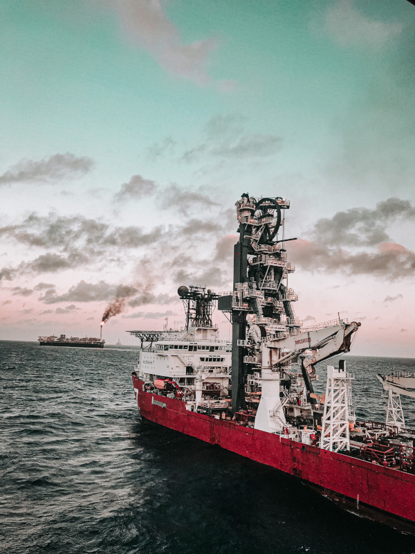 A red and white drillship is in the blue sea. A black ship is visible on the horizon. The sky is blue and pink, with a few gray clouds.