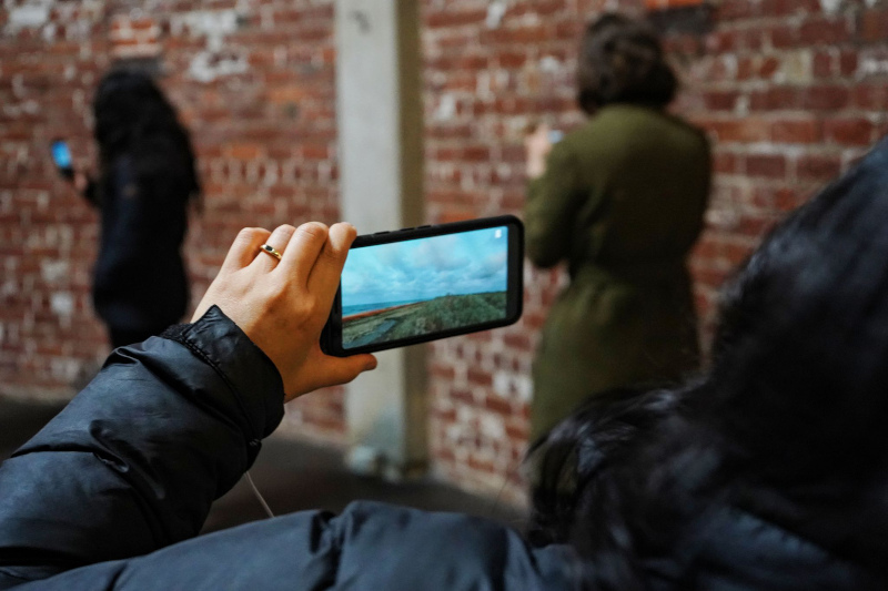 A woman points a smartphone at a brick wall and two other female figures. The screen of the phone shows a landscape with cloudy skies, water, and a green plain.