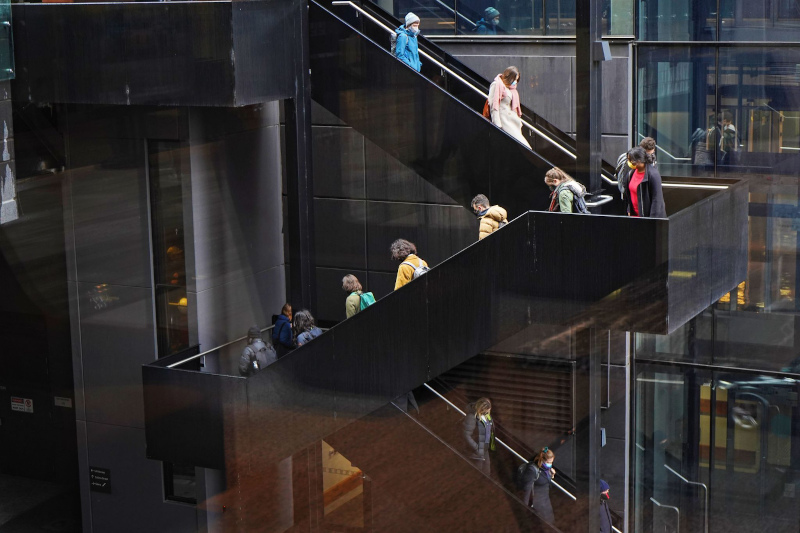 Thirteen workshop participants are walking down a metallic staircase
