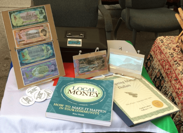 Laid out on a table are copies of the Salt Spring Dollar used within the community of British Columbia along with texts utilized by the author to aid her in gathering information regarding the SSD when doing her research.