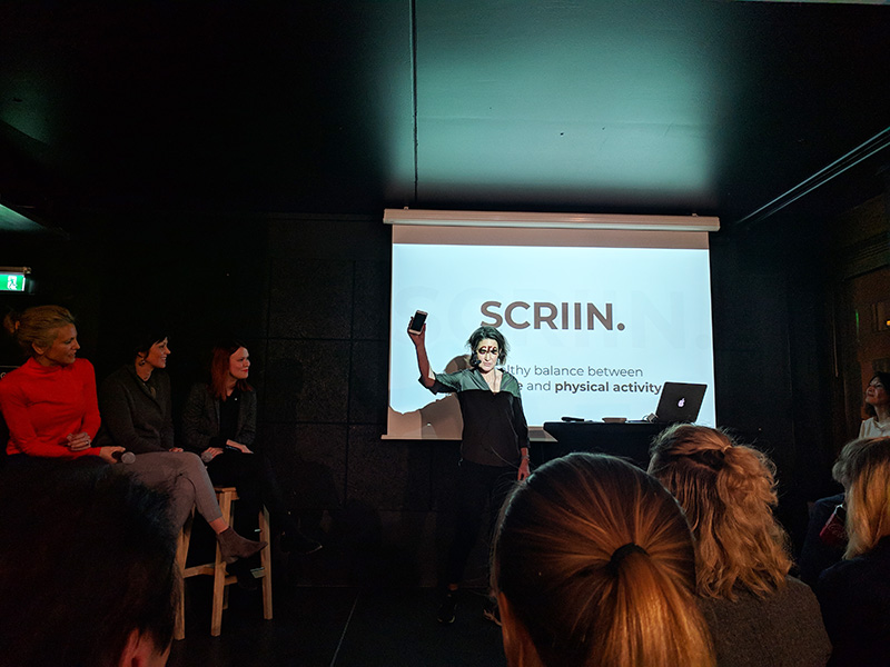"""Three women panelists are seated in tall chairs. A woman stands in front of a projector screen holding up a phone. The screen says """"SCRIIN""""."""