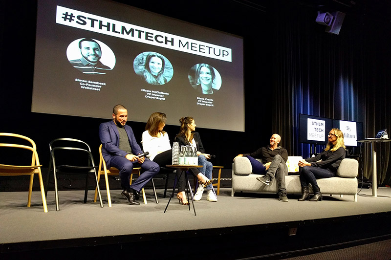 """Two co-hosts and three panelists sit in on stage. Behind them is a projection screen that says """"#STHLMTECH Meetup"""" and has photographs, the names, and titles of the three panelists."""