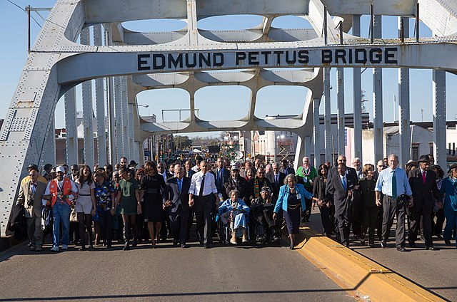 President Obama, congressman John Lewis, former President George W. Bush, and Civil Rights Movement veterans and other commemoration attendees marching across the Edmund Pettus Bridge in March, 2015