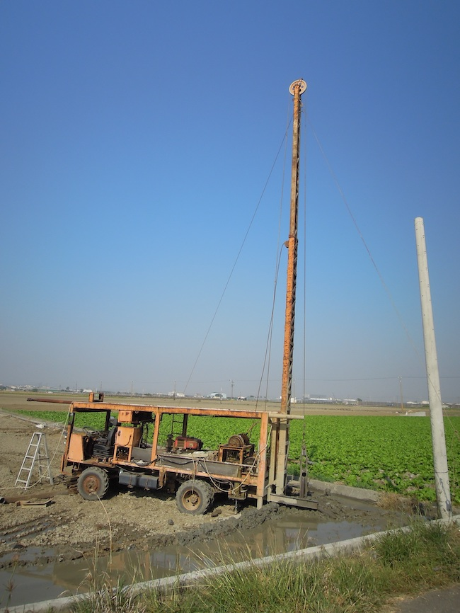 A machine sits atop mud in a field and is pounding an iron tube into the ground for the cutting process.