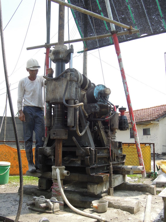 """A man operates a drill that is being used to """"core"""" and collect """"core"""" samples."""