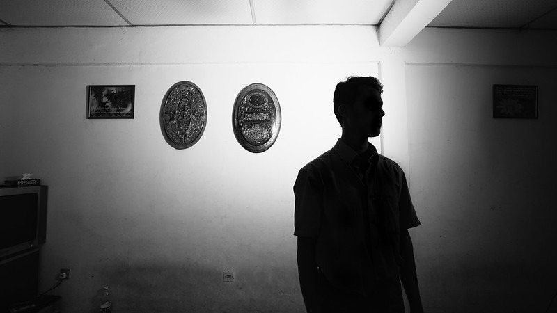 Image consists of a silhouette of a young man who is facing the camera. Behind him are a small series of decorative plates on the wall. The image is in black and white, and the profile of the man is not sharply visible. The man appears to be staring at something slightly away from the camera.