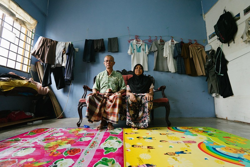 An older couple sits side-by-side on a small red sofa, against a light blue wall. The man wears a green shirt and a plaid sarong. The woman wears a black hijab and a flowery skirt. In front of the sofa are two brightly colored pink and yellow rugs, with green and black patterns. Behind the sofa are a number of pieces of clothing, hung up and spread out. There is a white wall on one end of the room, and a window with a square grill at the other end.
