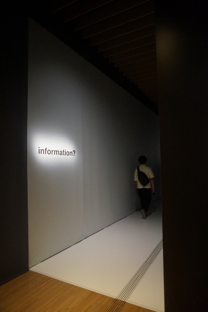 """A corridor at the beginning of the exhibition in the Suntory Museum of Art. It is dimly lit, with the word """"information?"""" lit up on the wall."""