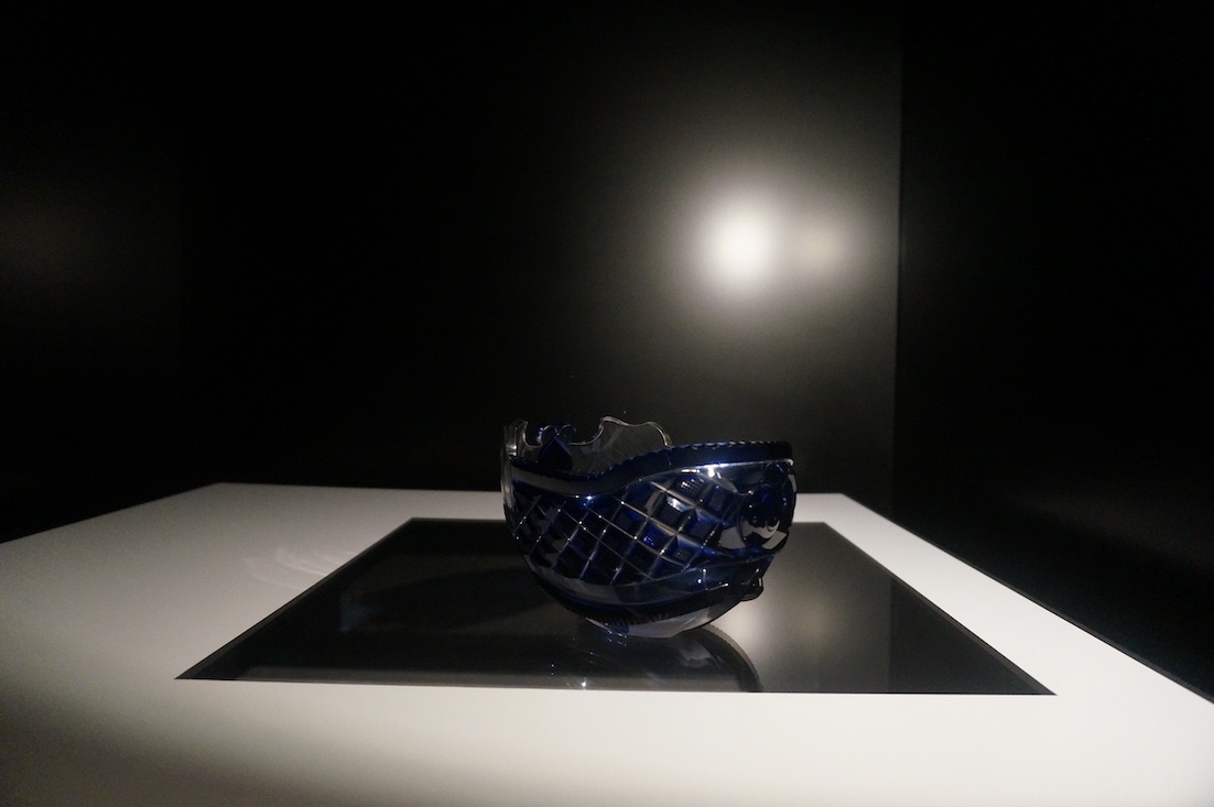 A glass cut boat shaped bowl with indigo-blue overlay sits upon a plain black surface.
